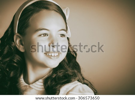Beautiful young girl dressed in white. First Communion. Perfect teeth and smile, long curly hair. Dark background, close up studio shoot. Sepia picture. - stock photo