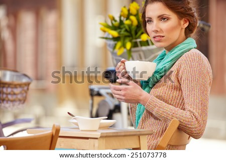 beautiful young girl drinking coffee in a old town cafe - outdoor portrait  - stock photo