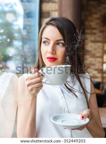 Beautiful young girl drinking coffee next to the window in the restaurant. Winter concept