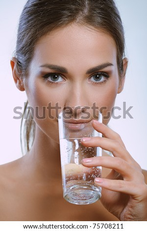 Beautiful young girl drinks water from glass