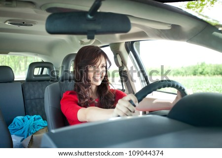 Beautiful young girl driving car