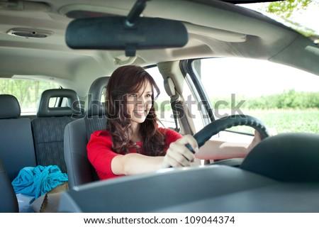 Beautiful young girl driving car - stock photo