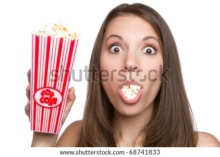 Beautiful young girl eating popcorn - stock photo