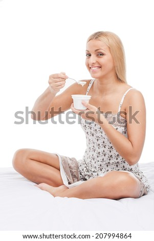 beautiful young girl eating yogurt. pretty blond sitting on bed and smiling - stock photo