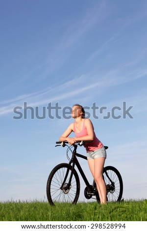 Beautiful young girl enjoys a ride on a bike outside - stock photo