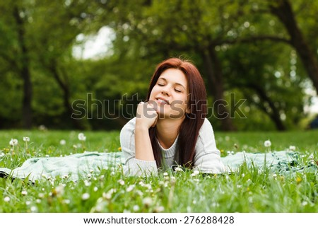 Beautiful young girl enjoys lying down in nature.Leisure time - stock photo