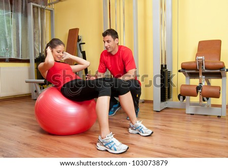 Beautiful young girl exercising abs in the gym under supervision of her coach. .