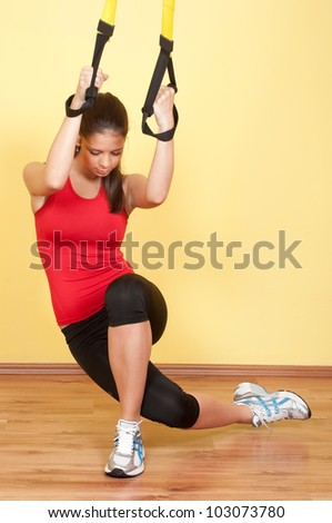 Beautiful young girl exercising in the gym with suspension device.