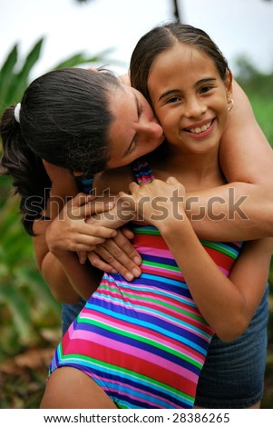 Beautiful, young girl gets hugged and kissed by her mom.