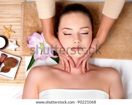Beautiful young girl getting massage for neck in spa salon - indoors - stock photo