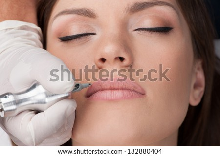 beautiful young girl getting tattoo. professional tattooist making permanent make up - stock photo