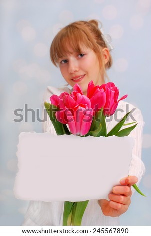 beautiful young girl giving bouquet of pink tulips and greeting card ( focus on flowers)