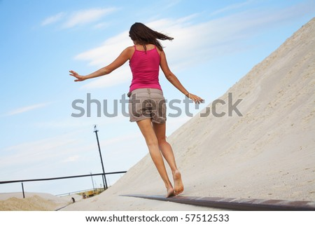 beautiful young girl goes on the rails balancing hands - stock photo