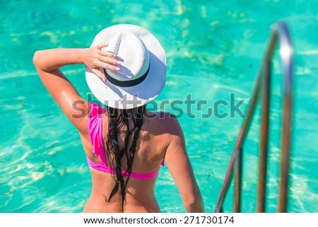 Beautiful young girl going to swim in the swimming pool - stock photo