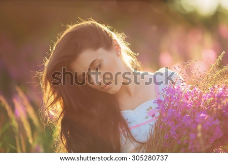 Beautiful young girl, happy, holding lavender in a field on sunset. walking field. Soft focus, close-up