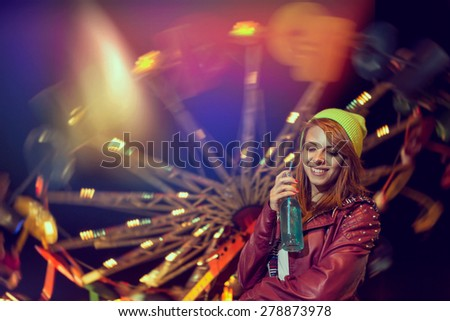 Beautiful young girl having fun and drinking juice at theme park - stock photo