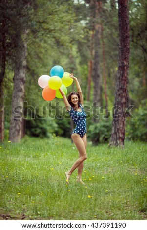 Beautiful young girl having fun at the summer park with colored balloons. Happy smile jump concept