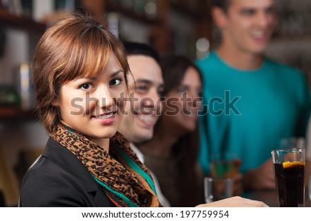 Beautiful young girl having fun in a bar with friends