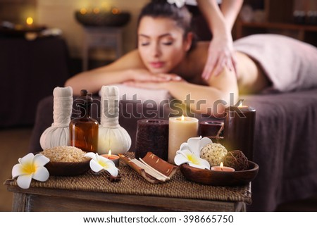 Beautiful young girl having massage and aromatic candles with salt in spa salon - stock photo