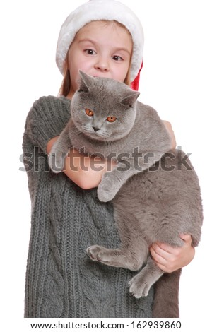 beautiful young girl holding adorable British cat on christmas background - stock photo