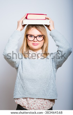 beautiful young girl holding books on his head, wearing glasses isolated
