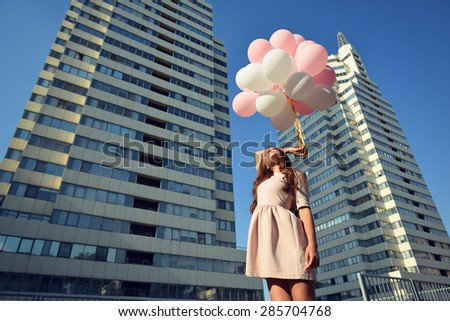 Beautiful young girl holding colored balloons over high-rise building. Urban teenage background. Toned. - stock photo