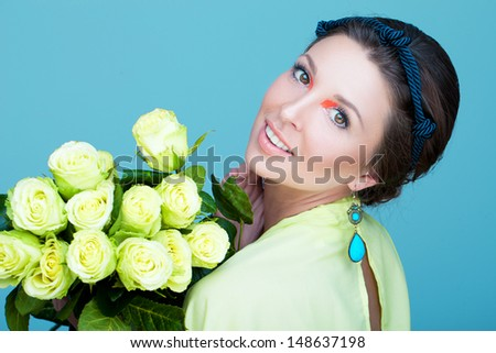 Beautiful young girl holding flowers - stock photo