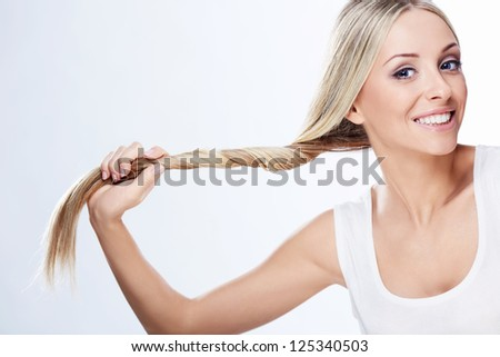 Beautiful young girl holding hair on a white background