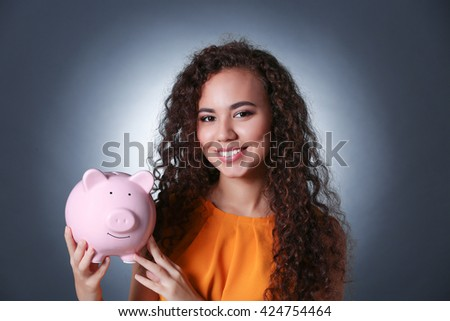 Beautiful young girl holding piggy bank on grey background