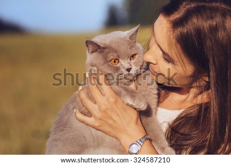 Beautiful young girl holds a British cat with orange eyes, outdoor, close-up   - stock photo
