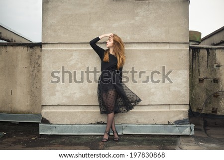beautiful young girl in a black dress on a windy day