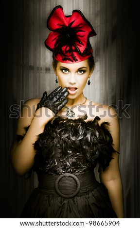 Beautiful young girl in a black feather cabaret outfit standing with her hand raised to her open mouth with a shocked and surprised expression - stock photo