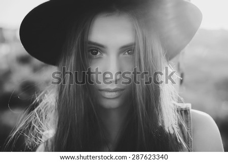 beautiful young girl in a black hat posing on the street and sad - stock photo