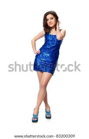 Beautiful young girl in a blue dress with sequins posing in studio isolated on white - stock photo