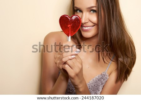 Beautiful young girl in a dressing gown of silk and lace with thin spaghetti straps with a cut and bow in front of hands holding lollipop in the shape of a red heart looking into camera valentines day - stock photo