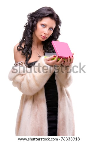 Beautiful young girl in a fur coat, holding a box
