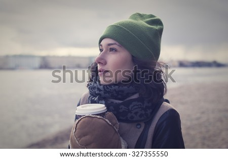 Beautiful young girl in a leather jacket with a cup of hot coffee in the city of St. Petersburg - stock photo