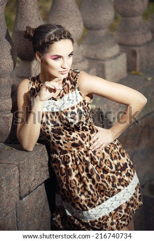 Beautiful young girl in a leopard print dress with a pink make-up on the background of the columns.