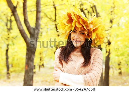 Beautiful young girl in a park in autumn, outdoors