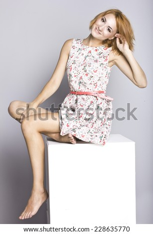 Beautiful young girl in a short dress. Portrait of a stylish red-haired girl in studio