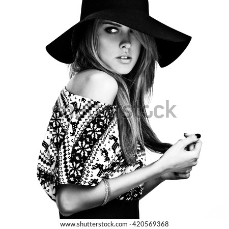 Beautiful young girl in a sweater with deer print and black hat. Black-white photo. - stock photo