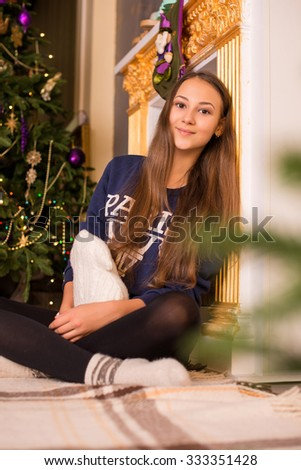 beautiful young girl in a sweatshirt and tights near the Christmas tree, Christmas lights in the background, she smiles, happy,white socks, warm socks, a white teddy bear, hugging a pillow, fireplace - stock photo