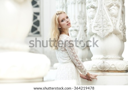 Beautiful young girl in a white lace dress outdoors - stock photo