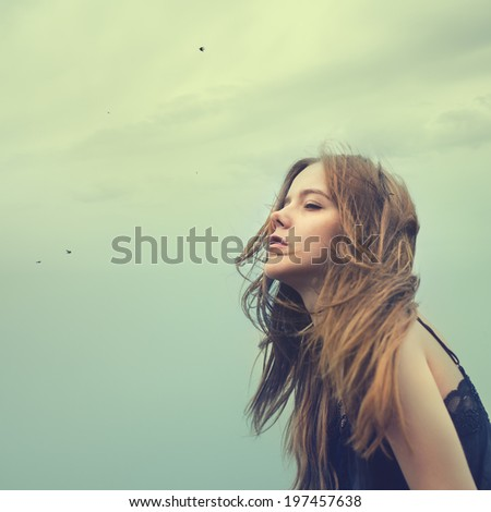 beautiful young girl in a windy day against the sky - stock photo