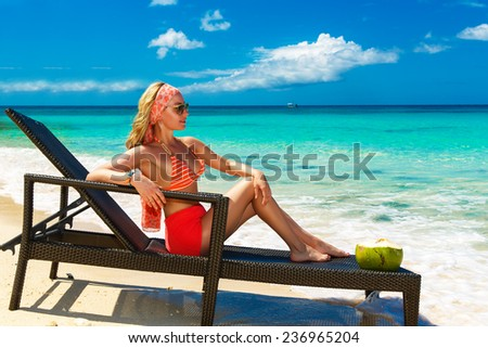 Beautiful young girl in bikini is sitting on a sun lounger coast of tropical sea. Summer vacation concept.