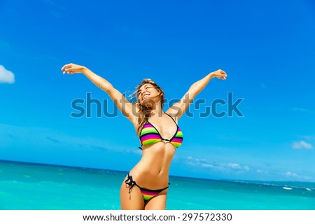 Beautiful young girl in bikini on a tropical beach. Blue sea in the background. Summer vacation concept. - stock photo