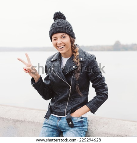 Beautiful young girl in black beanie saluting and winking. Outdoor lifestyle portrait of woman