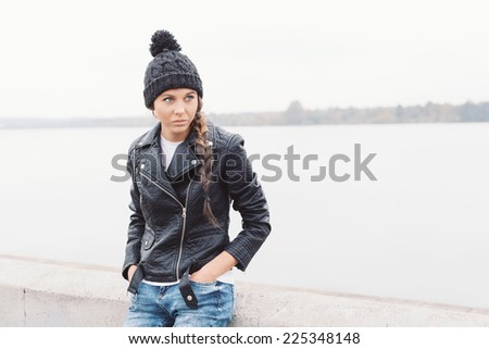 Beautiful young girl in black hat looking away and waiting someone. Outdoor lifestyle portrait of woman - stock photo
