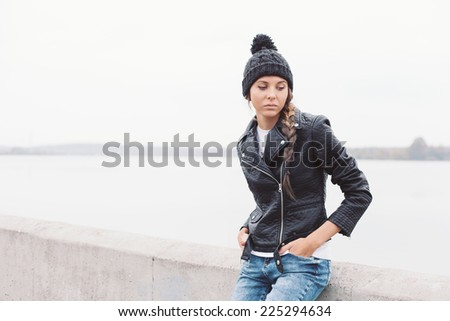 Beautiful young girl in black hat waiting someone. Outdoor lifestyle portrait of woman - stock photo