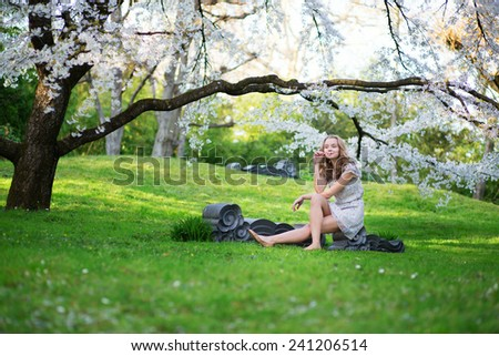 Beautiful young girl in blooming garden on a spring day